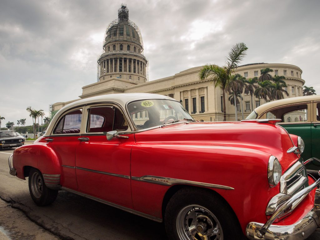 Red classic car in front of the Havana's Capitolio BY RUDY GIRON