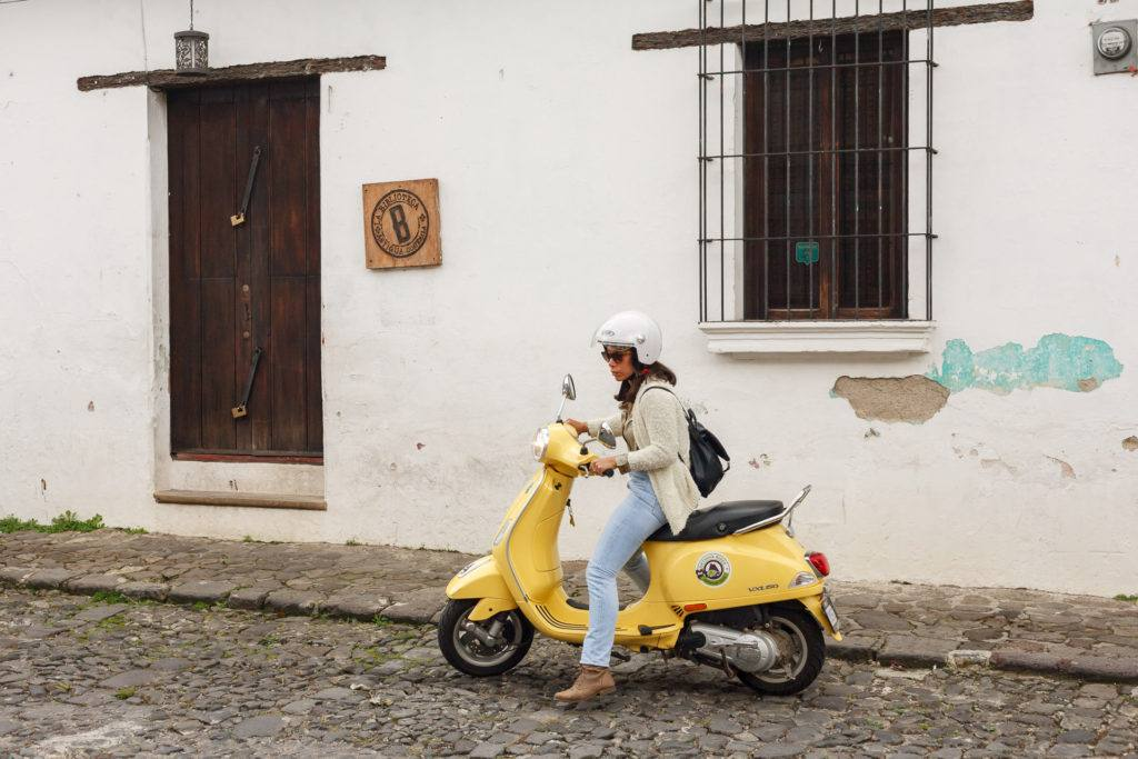 Woman on yellow scooter on the streets of Antigua Guatemala by RUDY GIRON