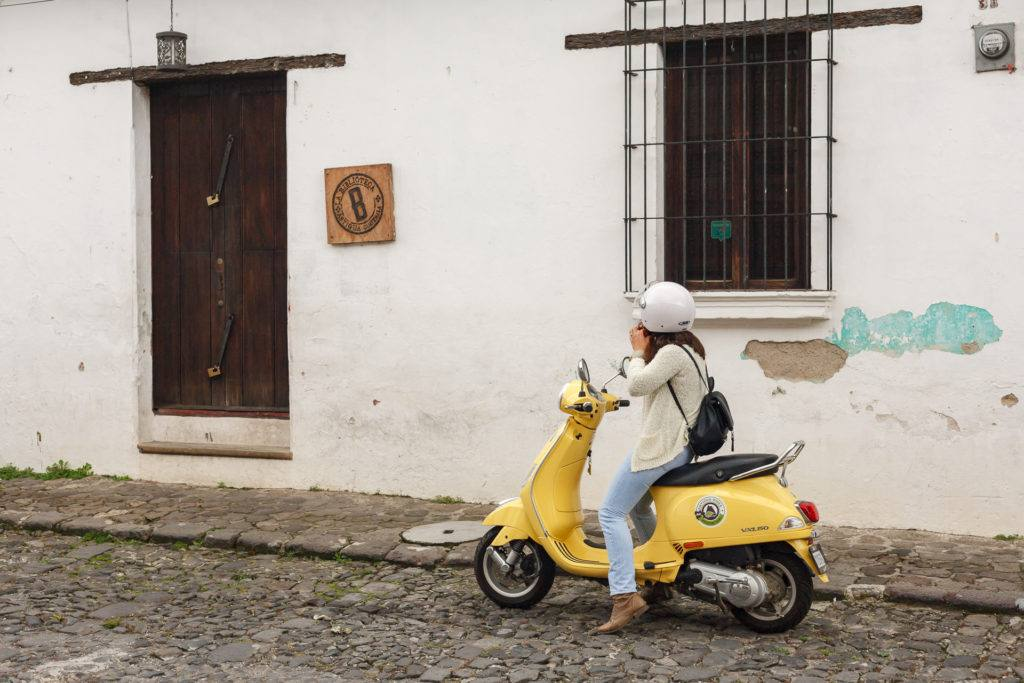 Woman putting on helmet on yellow scooter on the streets of Antigua by RUDY GIRON